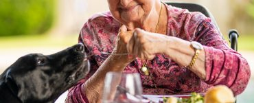 senior woman eats at table with dog standing by