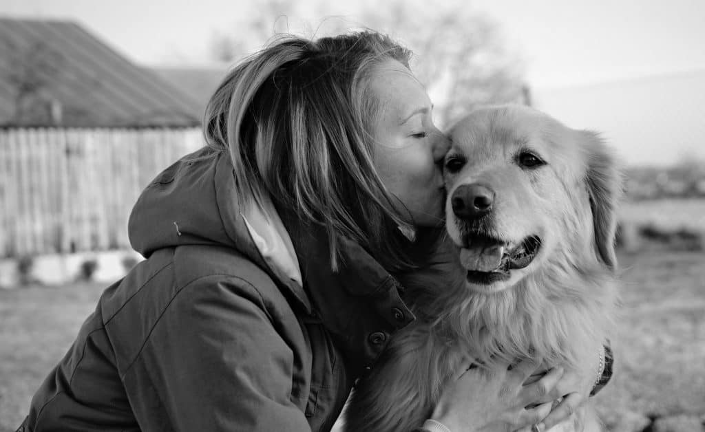 woman kisses her dog